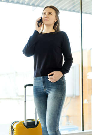 Young woman with mobile phone in the airport. Reklamní fotografie