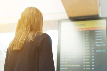 Woman in front of flight information board, checking her flight.