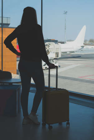 Young woman with luggage in the airport.