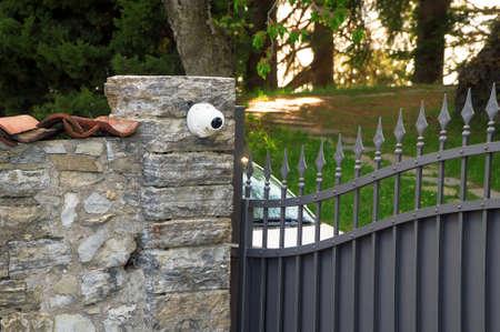 Metal gates and security camera. Private property. Фото со стока