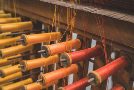 Many multi-colored spool of threads in a sewing factory.
