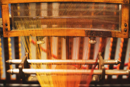 Very old loom machine with colored threads. Imagens