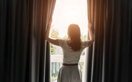 Woman opening curtains in the hotel room at sunny morning.