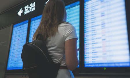 Mujer delante del tablero de información de vuelo, comprobando su vuelo.