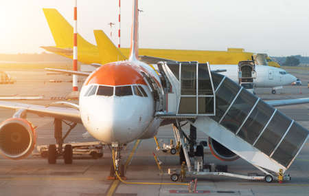 Passenger plane in the airport at sunrise. Aircraft maintenance. Stock fotó