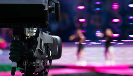 Professional video camera is filming live performance.