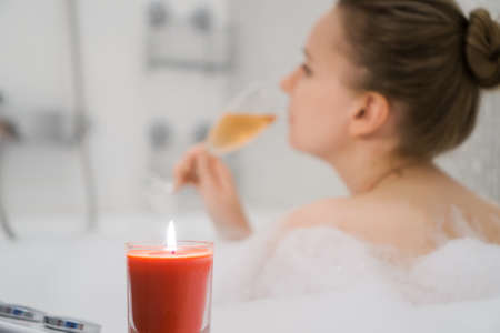 Woman with glass of wine is relaxing in bathtub.