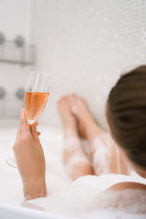 Woman with glass of wine is relaxing in bathtub. Rear view.