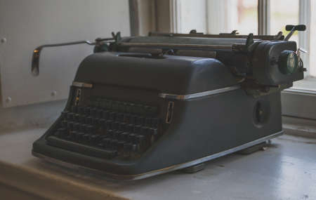 Old retro typewriter standing on the windowsill.