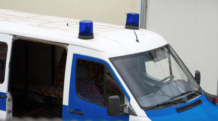 Police van with light bars on the street. Imagens