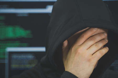 Hacker hiding his face. Hacking and internet security concept.