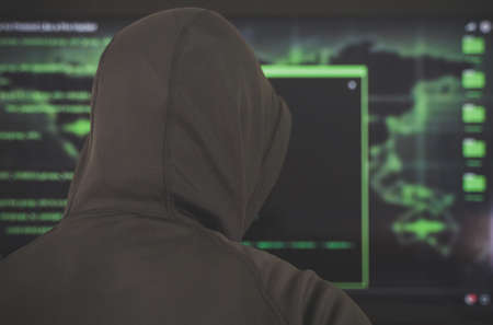 Hacker in black hoodie. Hacking and internet security concept.