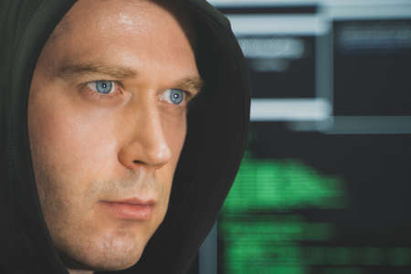 Handsome hacker in black hoodie. Hacking and internet security concept. 写真素材