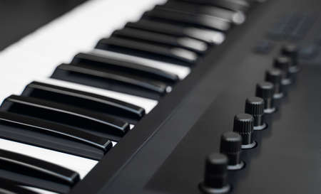 Professional midi keyboard synthesizer with knobs and controllers.