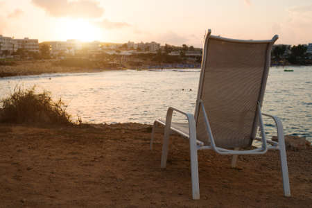 Sunbed in front of Fig Tree Beach in Protaras on sunset.