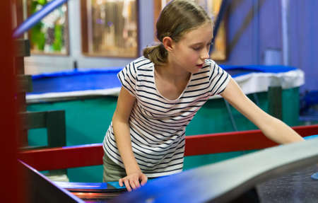 Little girl playing air hockey in amusement park.