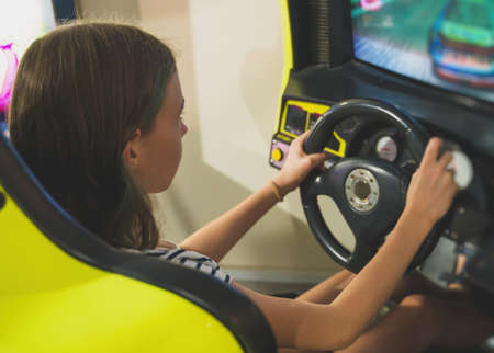 Little girl playing racing simulator game in theme park.