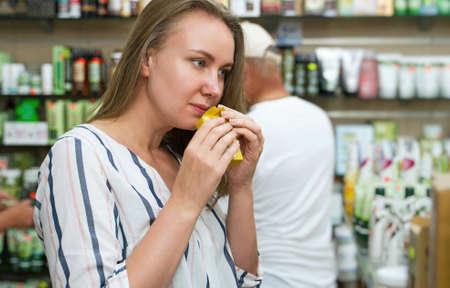 Young woman choosing soap in beauty shop.
