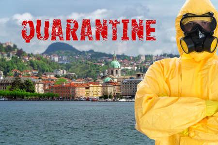 Man in biohazard suit. Como lake in Lombardy, Italy. Covid-19 quarantine concept. Archivio Fotografico