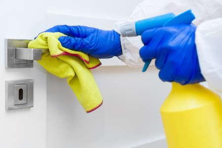 Hand in protective glove with rag cleaning door handle.