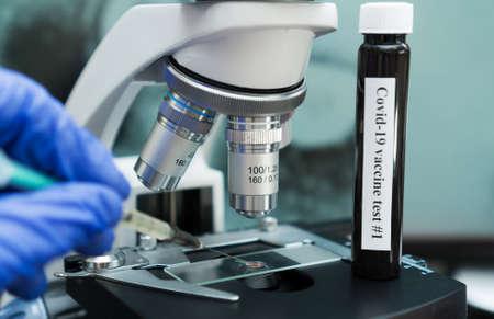 Virologist's hand in glove testing coronavirus vaccine under microscope. Foto de archivo