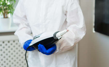 Cleaner in biohazard suit disinfecting room.