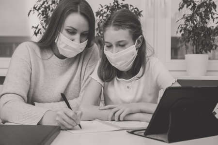 Schoolgirl with her mother at distance learning, doing homework. Home schooling concept.