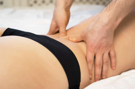 Male hands massaging woman's back at home.