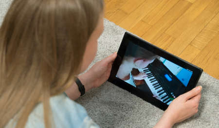 Teacher watches as girl plays the piano. Home schooling.