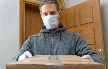 Courier in medical mask and gloves delivers package. Parcel delivery service.