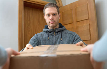 Male courier delivers package. Parcel delivery service. Stock Photo