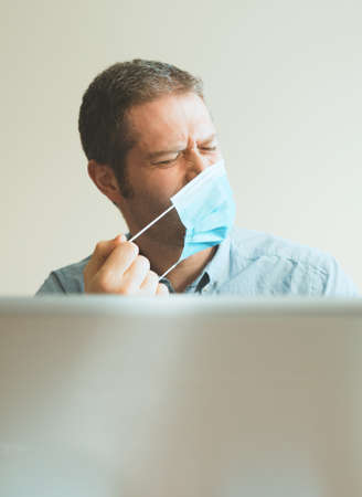 Man tired of wearing medical mask indoors.