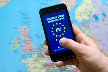 Man holding phone with European Immunity passport app. Travel during Covid-19 concept.