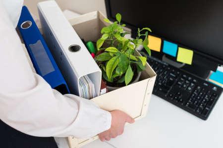 Businesswoman holding cardboard box with office stuff. Resignation concept. Фото со стока
