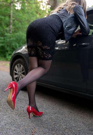 Frau flirtet in der Nähe des Autos des Kunden. Standard-Bild