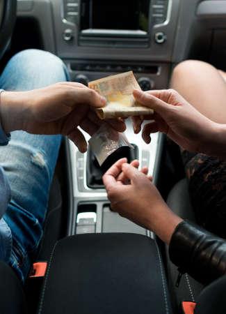 Drug dealer sells drugs to a prostitute inside the car.