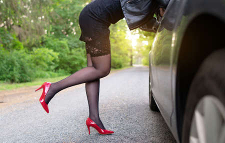 Female flirting near the client's car.