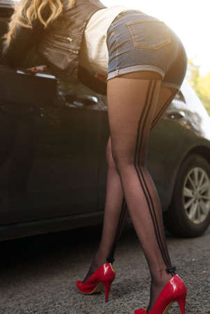 Female prostitute flirting near the client's car.