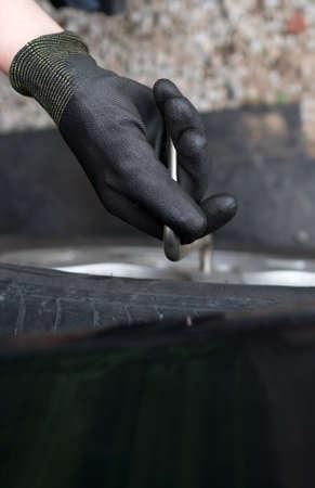 Woman changing car tire. Close-up view. 免版税图像 - 151118357