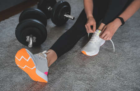 Woman tying shoelaces before exercise. Home fitness training concept.