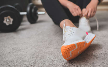 Woman tying shoelaces before exercise. Home fitness training concept. Banco de Imagens