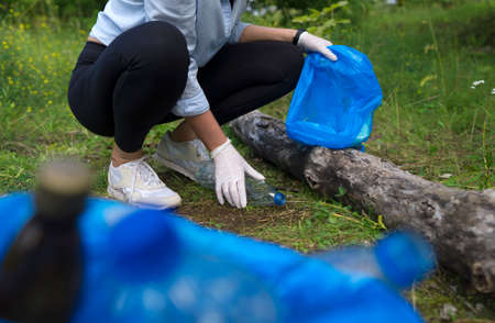 Volunteer collecting bottles in the forest. Environment pollution concept.