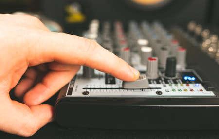 Sound engineer using main control fader of studio mixer. Stock Photo