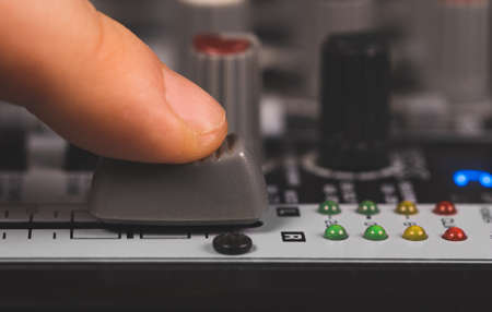 Sound engineer using main control fader of studio mixer.