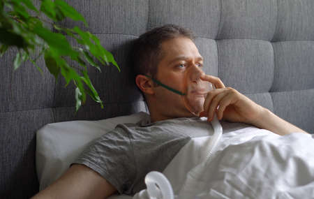 Sick man with inhalator mask on the face in bed. Coronavirus prevention concept. Stok Fotoğraf