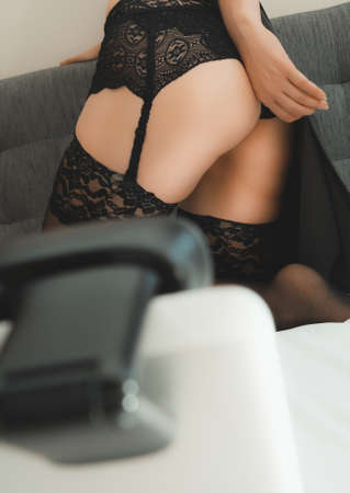 Seductive woman working as webcam model. Removing stockings. Stock Photo