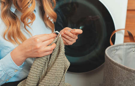 Woman looking at the tag on the clothes before loading clothes into washing machine. Stockfoto