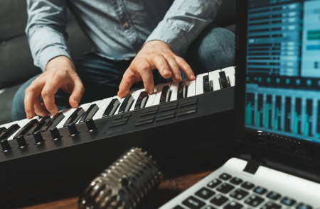 Man playing the piano in studio, recording new song on wooden table