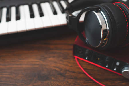 Piano, headphones and sound card on wooden table