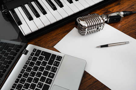 Music studio equipment and white paper with pen.